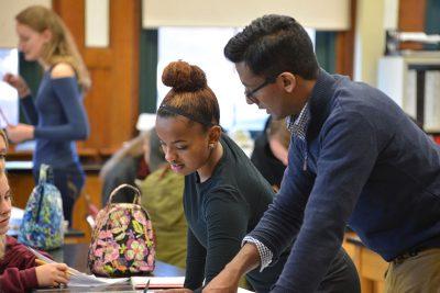 TCPCG grad Sushruta Kunnenkeri works with a student at NFA. [Links to profile piece on Sushruta.]